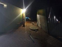 uszkodzony blaszany garaż w tle radiowóz policyjny